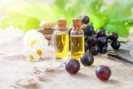 Essential oil of grape seeds on a wooden table - healing aromatic oil 写真素材