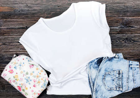 White Women's T-shirt on a Dark Wooden Background - Flat Lay, Ttop View