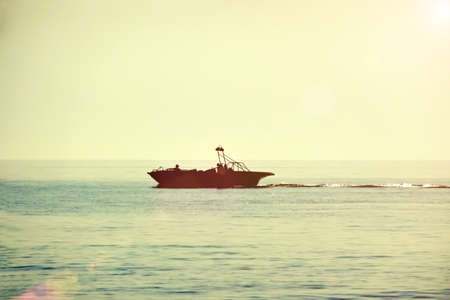 Fishing boat goes to sea on a summer day - toned photo 免版税图像 - 113450255
