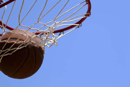 swish: Basketball going through net against blue sky