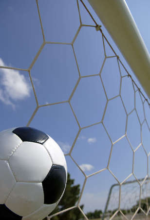 Soccer ball in goal with blue sky background