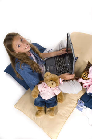 young girl working, playing on laptop computer photo