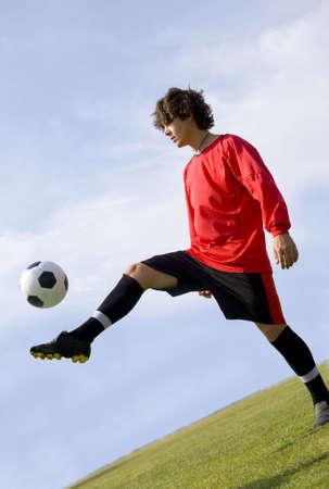coordinacion: F�tbol - jugador del balompi� que hace juegos malabares en un Uniforme rojo y negro
