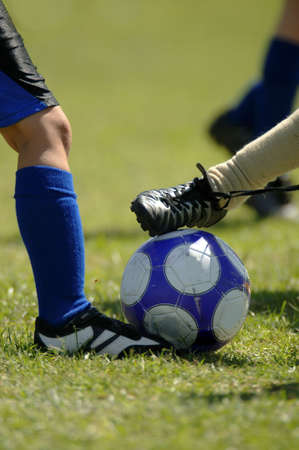 Several set of feet trying to control soccer ball - football Stock Photo - 452083