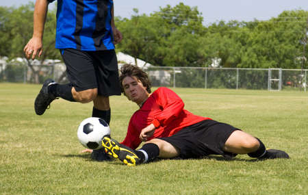 tackle: Football - Soccer player making sliding tackle