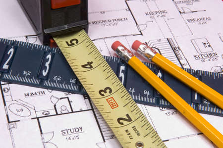 Measuring tape and ruler on red background and house floorplan