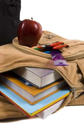 fournitures scolaires: brun �cole sac � dos rempli de fournitures scolaires avec du papier, des crayons et des dossiers, courdoroy, et une pomme  Banque d'images
