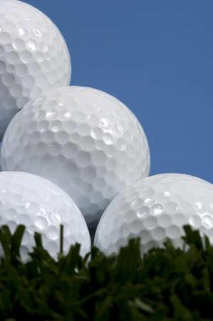 Golf ball pyramid on grass with blue sky