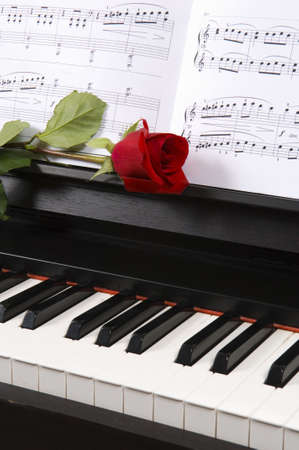 Sheet music with rose  on piano photo