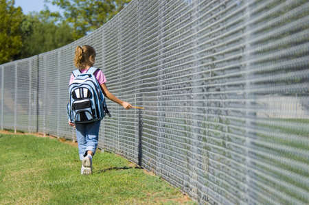 Little girl walking to school by school fence on beautiful sunny day wth back pack and pencil Stock Photo