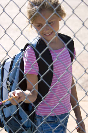 bookbag: Little girl walking to school by school fence on beautiful sunny day wth back pack and pencil Stock Photo