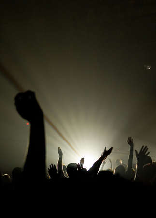 raising hand: christian music concert with raised hands with one person is center worshiping Stock Photo