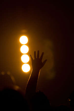 christian music concert with raised hands with one person is center worshiping Фото со стока