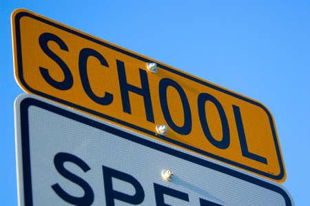 límite de velocidad firmar con la escuela especial de alerta en amarillo agianst cielo azul. S y C son ligeramente fuera de foco. atención se centra en el centro