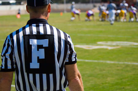 played: American Football played by young men with game official field judge referee
