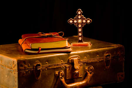 glint: Vendimia, art�culos religous antiguos pintados con la luz. Los art�culos del misionario incluyendo un foco de la biblia, del diario, de la maleta y de la cruz est�n en cruz con un glint de la luz en uno de los cristales en cruz