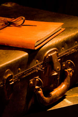 old, vintage, antique leather suitcase with leather bound and tied book on top painted with warm light Stock Photo