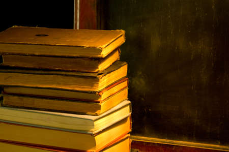 instructing: Antique, vintage,  old books sitting on ledge of olf antique black, chalk board at school Stock Photo