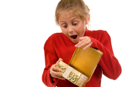 suprise: Young gil in red sweater opening Christmas gift wrapped in gold with a look of suprise and excitement Stock Photo