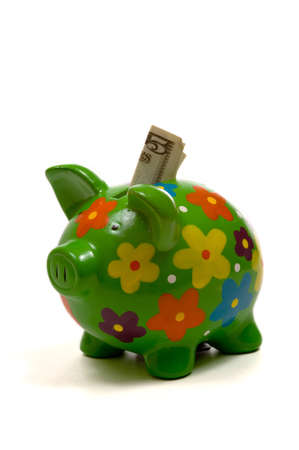 green, brightly colored piggy bank with money sticking out the top on white photo