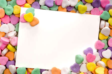 white notecard surrounded by candy conversation hearts- blank Stock Photo