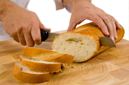 slicing: slicing bread on wood cutting board with a bread knife