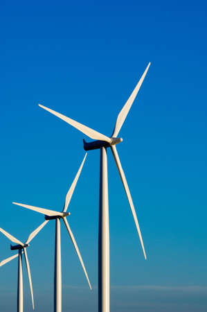 Modern white wind turbines or wind mills producing energy to power a city Imagens