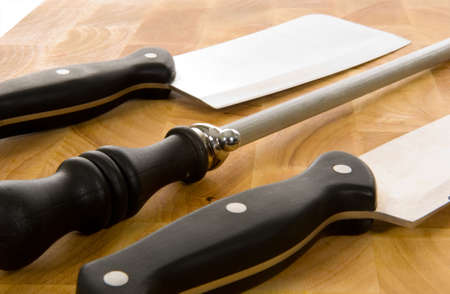 the cleaver: Kitchen knives including chefs knife, cleaver and sharpening steel on wooden cutting board Stock Photo