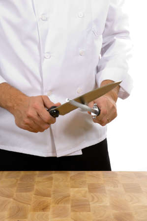 honing: Professional chef (man) sharpening knife with steel