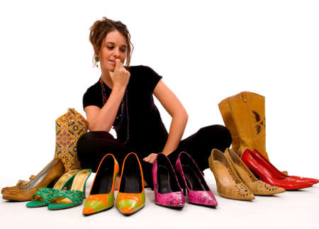 overwhelm: Young pretty lady trys to decide what shoes to wear, decisions Stock Photo