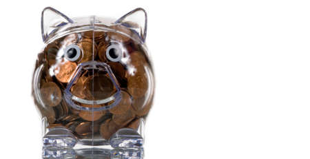 pennies: Clear plastic piggy bank stuffed full of pennies Stock Photo
