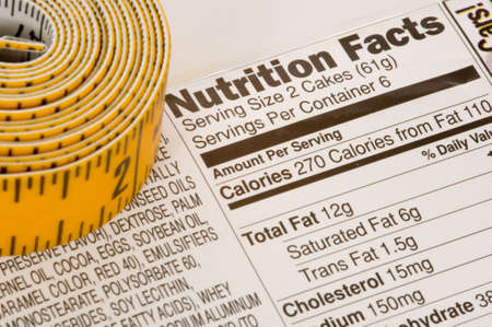 counting: Yellow tape measure next to nutrition information on packaging in the USA Stock Photo