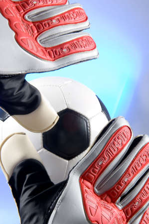 Soccer - Football goal keeper with gloves reaching for ball with blue background