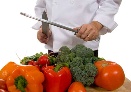 prep: Professional chef sharpening knife inlcluding assorted fresh vegetables Stock Photo