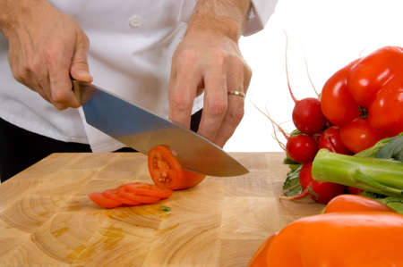 Professional chef slicing roma tomato on white background Reklamní fotografie