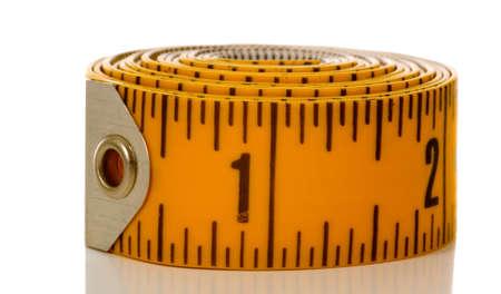 白い背景の上の黄色のテープ メジャーのクローズ アップ