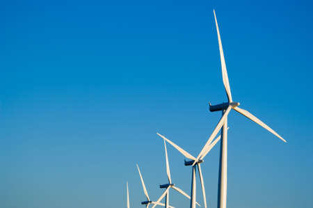 Modern white wind turbines or wind mills producing energy to power a city Stock Photo