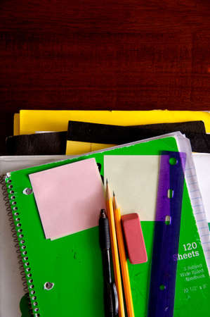 Used school supplies on desk with pencils, erasers, a ruler and post it notes Stock Photo - 896877