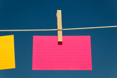 blank Pink index card on a clothesline with blue sky background