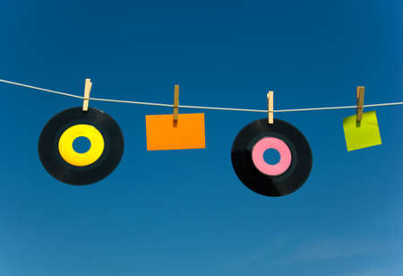 blank media on clotheline against blue sky, notecard and 45rpm records
