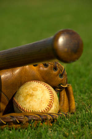 Vintage baseball with bat and glove on grass field photo