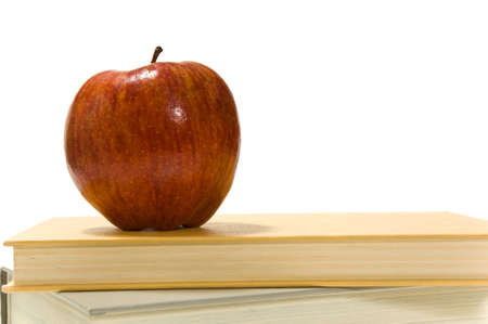 Several school books and an apple in front of and on white background
