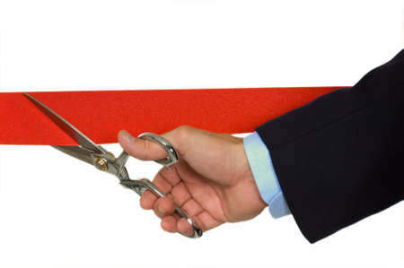 shiny suit: Closeup of a mans hand in a blue business suit cutting a red ribbon with shiny scissors- focus on ribbon Stock Photo