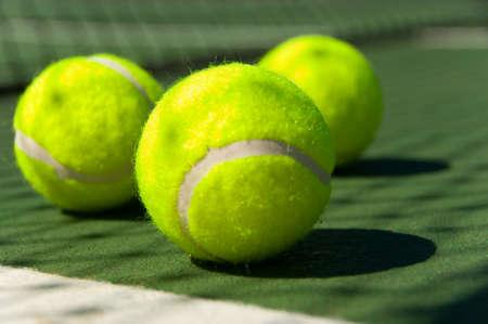 greenish: Bright greenish, yellow tennis balls on freshly painted cement court