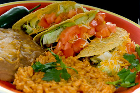 Mexican food plate with tacos, bean and rice on brightly colored plate Stock fotó