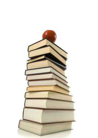 Huge stack of books with a shiny red apple on top on white backround