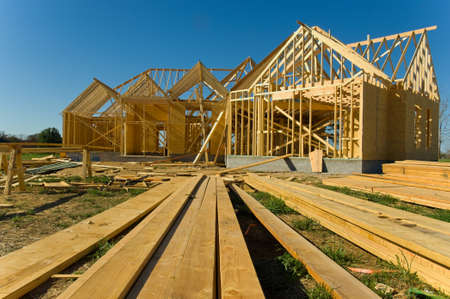 work from home: New home under construction with wood, trusses and supplies against blue sky
