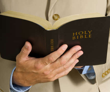 Man in business suit or preacher holding the BIble