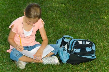Young girl in park doing school work Imagens