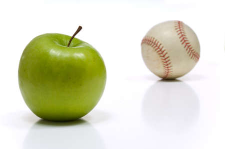 granny smith: Green granny smith apple and a baseball on white background,  symbols of summertime in America